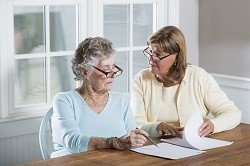 Two older ladies doing paperwork on a wooden table.