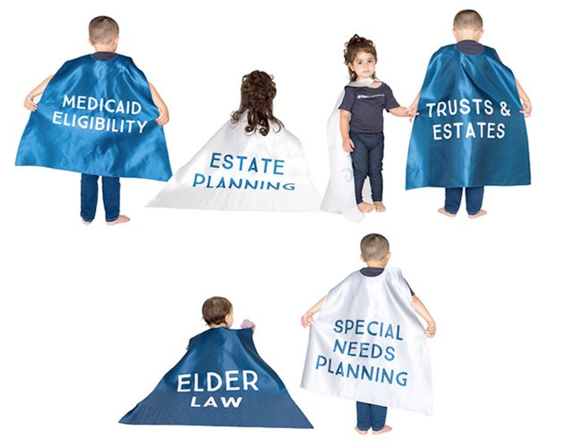 Photo of kids wearing blue & white capes with elder law services written on them.