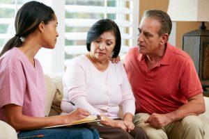 Female Nurse Making Notes During Home Visit With Senior Hispanic Couple
