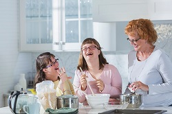 mother-and-two-daughters-with-down-syndrome-baking-in-page resized